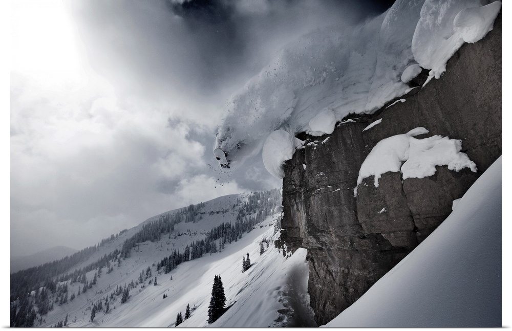 Poster Print Wall Art entitled A snowboarder does a half cab off a cliff on a