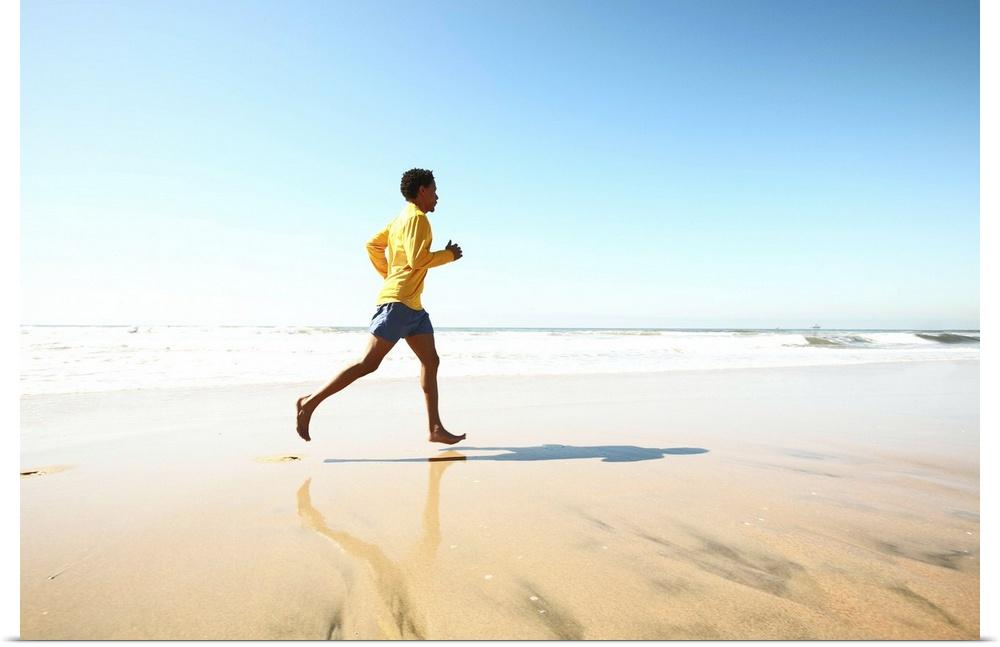 Poster Print Wall Art entitled Man jogging on beach