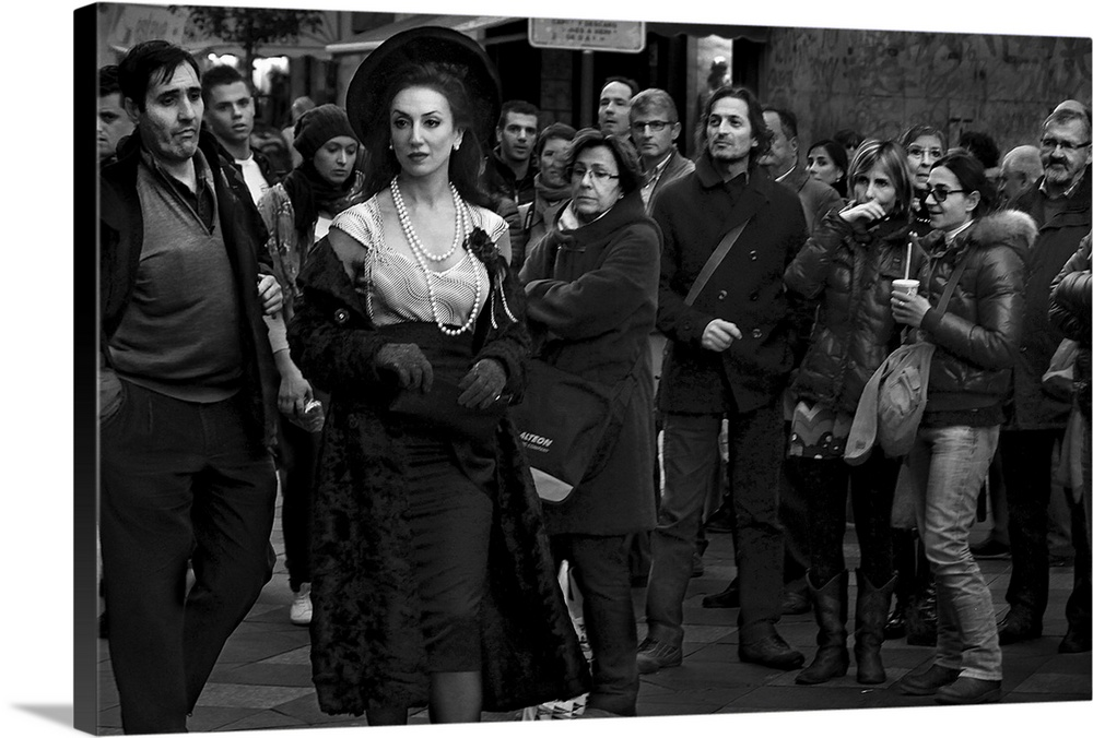 Large Solid-Faced Canvas Print Wall Art Print 30 x 20 entitled Mad Seven Solid-Faced Canvas Print entitled Mad Seven.  A woman with pearls and an elegant dress appears out of place among a crowd of people in everyday clothes.  Multiple sizes available.  Primary colors within this image include Dark Gray, Light Gray.  Made in USA.  Satisfaction guaranteed.  Inks used are latex-based and designed to last.  Featuring a proprietary design, our canvases produce the tightest corners without any bubbles, ripples, or bumps and will not warp or sag over time.  Archival inks prevent fading and preserve as much fine detail as possible with no over-saturation or color shifting.
