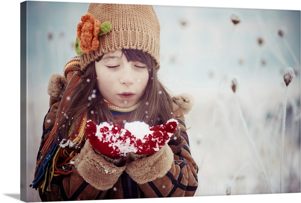 Large Solid-Faced Canvas Print Wall Art Print 30 x 20 entitled Snowflakes Solid-Faced Canvas Print entitled Snowflakes.  A young girl in winter clothes blows on a handful of snow.  Multiple sizes available.  Primary colors within this image include Dark Red, Black, Gray, Silver.  Made in the USA.  Satisfaction guaranteed.  Archival-quality UV-resistant inks.  Featuring a proprietary design, our canvases produce the tightest corners without any bubbles, ripples, or bumps and will not warp or sag over time.  Archival inks prevent fading and preserve as much fine detail as possible with no over-saturation or color shifting.
