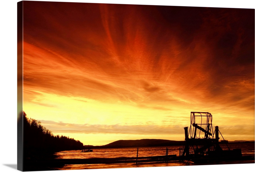 Large Solid-Faced Canvas Print Wall Art Print 30 x 20 entitled A fish wheel spins during sunrise on the Tanana River near ... Solid-Faced Canvas Print entitled A fish wheel spins during sunrise on the Tanana River near the village of Tanana, Alaska.  A fish wheel spins during an early morning sunrise on the Tanana River near the village of Tanana.  Interior, Alaska summer.  Multiple sizes available.  Primary colors within this image include Orange, Dark Red, Light Yellow, Black.  Made in the USA.  All products come with a 365 day workmanship guarantee.  Archival-quality UV-resistant inks.  Canvas depth is 1.25 and includes a finished backing with pre-installed hanging hardware.  Canvas is handcrafted and made-to-order in the United States using high quality artist-grade canvas.