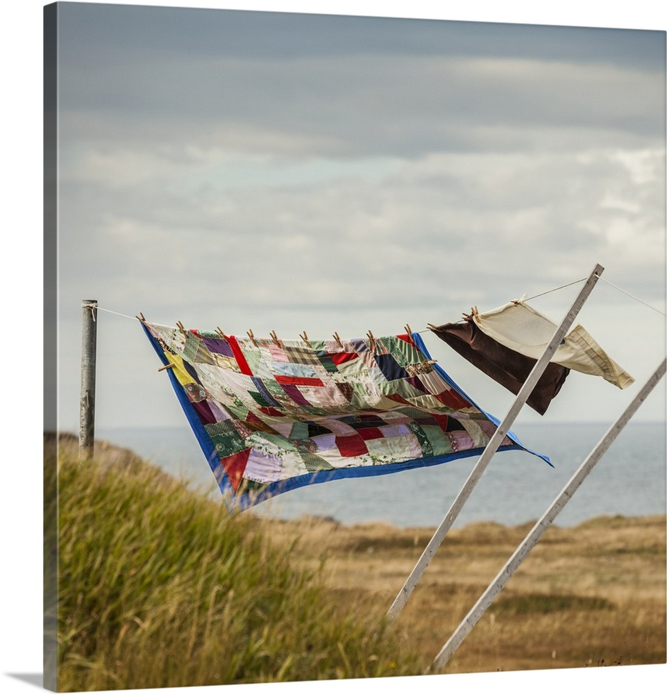 Large Solid-Faced Canvas Print Wall Art Print 20 x 20 entitled A patchwork blanket and pillow cases hanging on a clothesli... Solid-Faced Canvas Print entitled A patchwork blanket and pillow cases hanging on a clothesline with the Atlantic ocean.  A patchwork blanket and pillow cases hanging on a clothesline with the Atlantic ocean in the background Newfoundland, Canada.  Multiple sizes available.  Primary colors within this image include Plum, Silver, Muted Blue, Dark Forest Green.  Made in the USA.  Satisfaction guaranteed.  Archival-quality UV-resistant inks.  Archival inks prevent fading and preserve as much fine detail as possible with no over-saturation or color shifting.  Canvas depth is 1.25 and includes a finished backing with pre-installed hanging hardware.