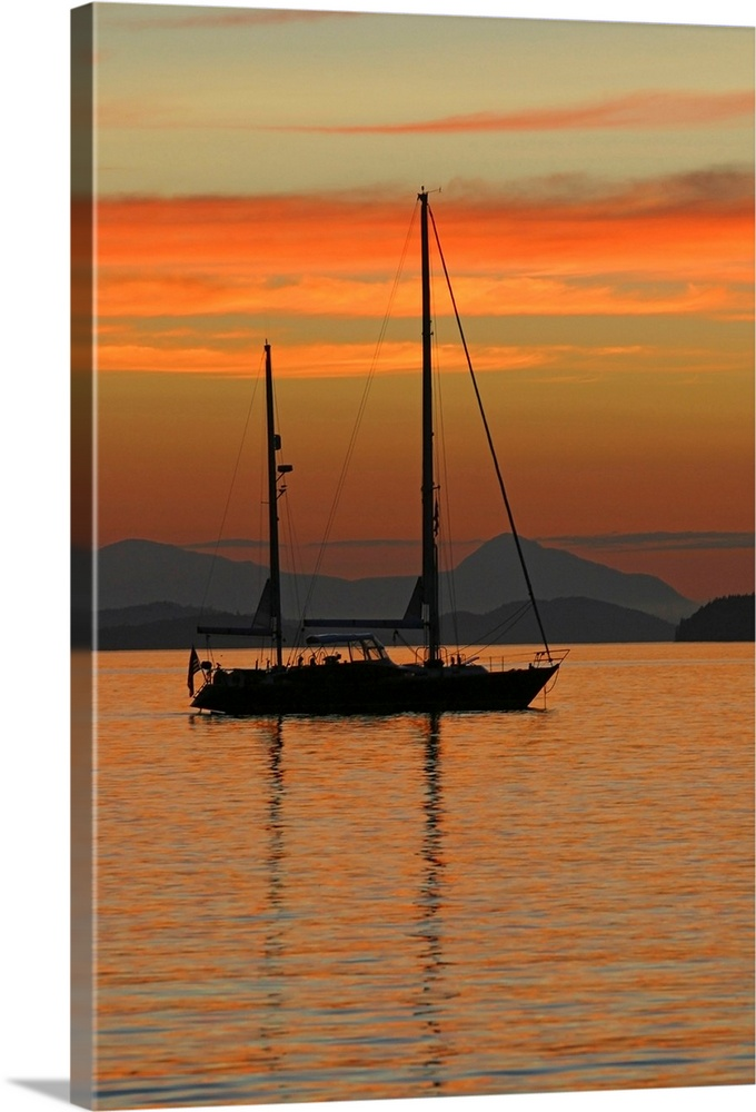 Large Solid-Faced Canvas Print Wall Art Print 20 x 30 entitled A sailboat is anchored for the night in the Gulf Islands of... Solid-Faced Canvas Print entitled A sailboat is anchored for the night in the Gulf Islands of British Columbia.  Beautiful photograph of a sail boat sitting in the water with mountains in the background as the sun sets and lights up the sky with warm tones.  Multiple sizes available.  Primary colors within this image include Orange, Dark Red, Peach, Black.  Made in USA.  All products come with a 365 day workmanship guarantee.  Archival-quality UV-resistant inks.  Archival inks prevent fading and preserve as much fine detail as possible with no over-saturation or color shifting.  Featuring a proprietary design, our canvases produce the tightest corners without any bubbles, ripples, or bumps and will not warp or sag over time.