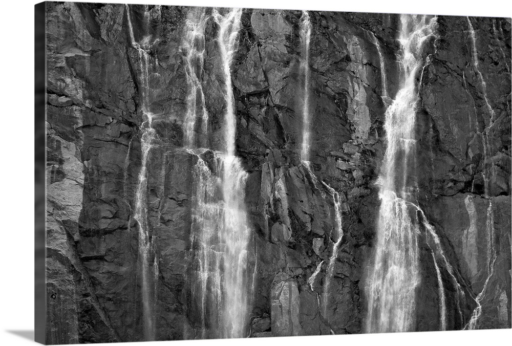 Large Solid-Faced Canvas Print Wall Art Print 30 x 20 entitled A waterfall cascades over rock cliffs on the Juneau Ice Fie... Solid-Faced Canvas Print entitled A waterfall cascades over rock cliffs on the Juneau Ice Field in Southeast Alaska.  Multiple sizes available.  Primary colors within this image include Dark Gray, Silver.  Made in USA.  All products come with a 365 day workmanship guarantee.  Inks used are latex-based and designed to last.  Canvas is handcrafted and made-to-order in the United States using high quality artist-grade canvas.  Featuring a proprietary design, our canvases produce the tightest corners without any bubbles, ripples, or bumps and will not warp or sag over time.