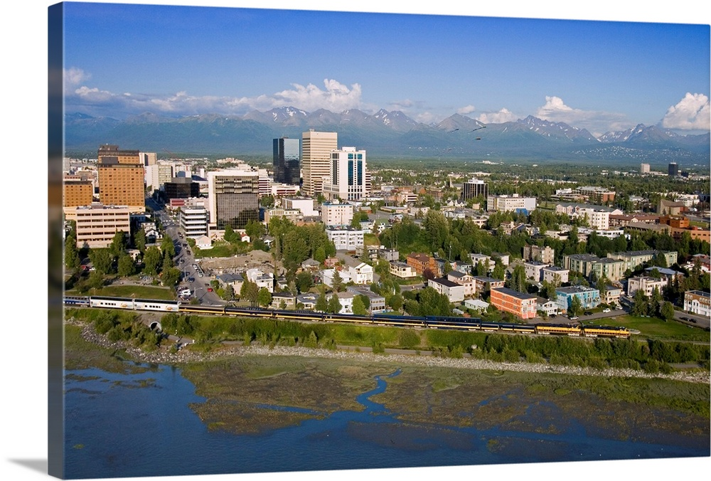 Large Solid-Faced Canvas Print Wall Art Print 30 x 20 entitled Aerial of Downtown Anchorage with Chugach Mtns in distance,... Solid-Faced Canvas Print entitled Aerial of Downtown Anchorage with Chugach Mtns in distance, Southcentral Alaska Summer.  Multiple sizes available.  Primary colors within this image include Peach, Sky Blue, Black, Dark Forest Green.  Made in USA.  Satisfaction guaranteed.  Inks used are latex-based and designed to last.  Canvas is handcrafted and made-to-order in the United States using high quality artist-grade canvas.  Canvas depth is 1.25 and includes a finished backing with pre-installed hanging hardware.