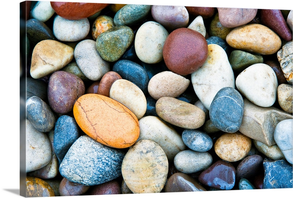 Large Solid-Faced Canvas Print Wall Art Print 30 x 20 entitled Close Up of multi colored stones Solid-Faced Canvas Print entitled Close Up of multi colored stones.  A horizontal photograph of smooth river stones piled on a beach. This calming photograph would make a wonderful decorative accent in a room with a natural color palette.  Multiple sizes available.  Primary colors within this image include Orange, Brown, Peach, Muted Blue.  Made in the USA.  Satisfaction guaranteed.  Inks used are latex-based and designed to last.  Canvas is handcrafted and made-to-order in the United States using high quality artist-grade canvas.  Archival inks prevent fading and preserve as much fine detail as possible with no over-saturation or color shifting.
