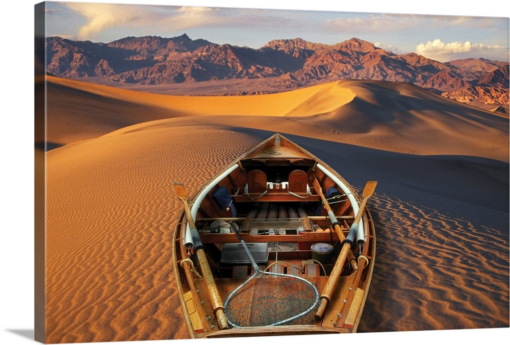 Large Solid-Faced Canvas Print Wall Art Print 30 x 20 entitled Drift boat resting on sand dunes in Death Valley National Park Solid-Faced Canvas Print entitled Drift boat resting on sand dunes in Death Valley National Park.  Drift boat and Death Valley National Park sand dunes. Composite.  Multiple sizes available.  Primary colors within this image include Brown, Peach, Black, White.  Made in USA.  Satisfaction guaranteed.  Inks used are latex-based and designed to last.  Canvas is handcrafted and made-to-order in the United States using high quality artist-grade canvas.  Canvas depth is 1.25 and includes a finished backing with pre-installed hanging hardware.