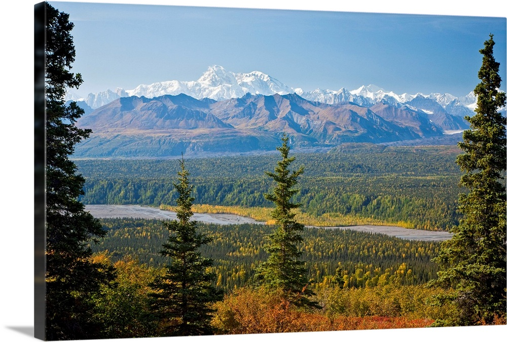 Large Solid-Faced Canvas Print Wall Art Print 30 x 20 entitled Large forest border swift river and mountain range with Mt.... Solid-Faced Canvas Print entitled Large forest border swift river and mountain range with Mt. Mckinley in the distance.  Multiple sizes available.  Primary colors within this image include Brown, Black, White, Royal Blue.  Made in the USA.  All products come with a 365 day workmanship guarantee.  Archival-quality UV-resistant inks.  Archival inks prevent fading and preserve as much fine detail as possible with no over-saturation or color shifting.  Featuring a proprietary design, our canvases produce the tightest corners without any bubbles, ripples, or bumps and will not warp or sag over time.