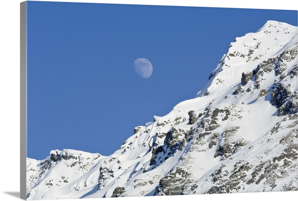 Large Solid-Faced Canvas Print Wall Art Print 30 x 20 entitled Moon rising over snow covered mountain peak at Hatcher Pass... Solid-Faced Canvas Print entitled Moon rising over snow covered mountain peak at Hatcher Pass in Southcentral Alaska.  Moon rising over snow covered mountain peak at Hatcher Pass in Southcentral Alaska.  Multiple sizes available.  Primary colors within this image include Dark Gray, Silver, Royal Blue.  Made in USA.  All products come with a 365 day workmanship guarantee.  Archival-quality UV-resistant inks.  Canvas is handcrafted and made-to-order in the United States using high quality artist-grade canvas.  Featuring a proprietary design, our canvases produce the tightest corners without any bubbles, ripples, or bumps and will not warp or sag over time.