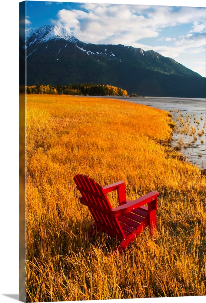 Large Solid-Faced Canvas Print Wall Art Print 20 x 30 entitled Red Adirondack chair, Southcentral Alaska Solid-Faced Canvas Print entitled Red Adirondack chair, Southcentral Alaska.  Vertical, large photograph of a single adirondack chair sitting at the edge of a grassy coastline, looking toward the water.  A large, snow capped mountain looms in the background, in South-central Alaska.  Multiple sizes available.  Primary colors within this image include Orange, Dark Red, Brown, Black.  Made in the USA.  All products come with a 365 day workmanship guarantee.  Inks used are latex-based and designed to last.  Archival inks prevent fading and preserve as much fine detail as possible with no over-saturation or color shifting.  Canvas depth is 1.25 and includes a finished backing with pre-installed hanging hardware.