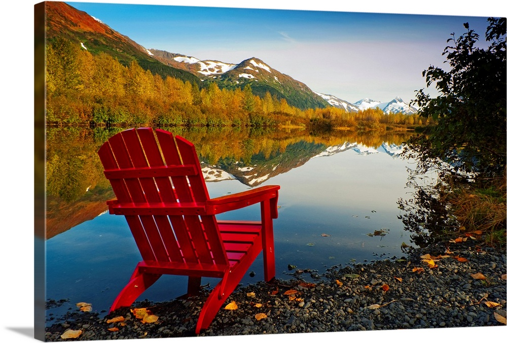 Large Solid-Faced Canvas Print Wall Art Print 30 x 20 entitled Red Adirondak chair along lakeshore, Alaska Solid-Faced Canvas Print entitled Red Adirondak chair along lakeshore, Alaska.  Landscape photograph on a big canvas of a red Adirondack chair sitting at the edge of a lake that is surrounded by trees.  Snow covered mountains in the background, in the wilds of Alaska.  Multiple sizes available.  Primary colors within this image include Dark Red, Brown, Black, White.  Made in USA.  All products come with a 365 day workmanship guarantee.  Archival-quality UV-resistant inks.  Canvas is handcrafted and made-to-order in the United States using high quality artist-grade canvas.  Featuring a proprietary design, our canvases produce the tightest corners without any bubbles, ripples, or bumps and will not warp or sag over time.
