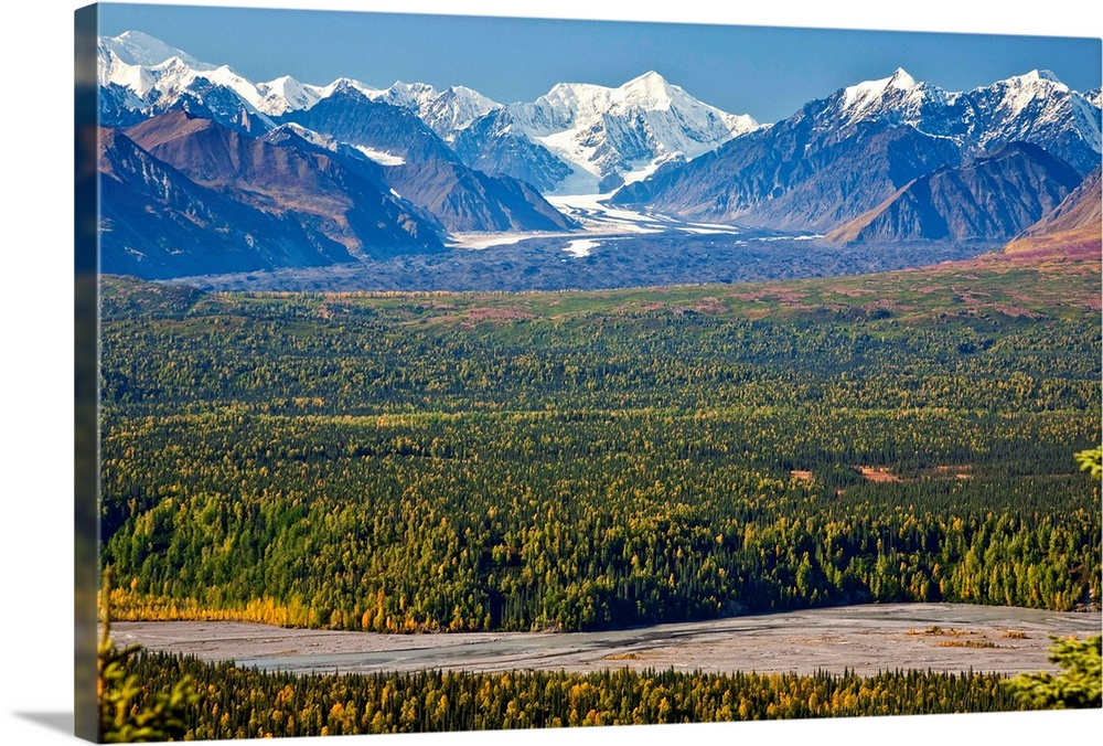 Large Solid-Faced Canvas Print Wall Art Print 30 x 20 entitled River runs through dense forest near Alaskan mountains Solid-Faced Canvas Print entitled River runs through dense forest near Alaskan mountains.  Multiple sizes available.  Primary colors within this image include Dark Yellow, White, Royal Blue, Dark Navy Blue.  Made in the USA.  All products come with a 365 day workmanship guarantee.  Archival-quality UV-resistant inks.  Canvas is handcrafted and made-to-order in the United States using high quality artist-grade canvas.  Featuring a proprietary design, our canvases produce the tightest corners without any bubbles, ripples, or bumps and will not warp or sag over time.
