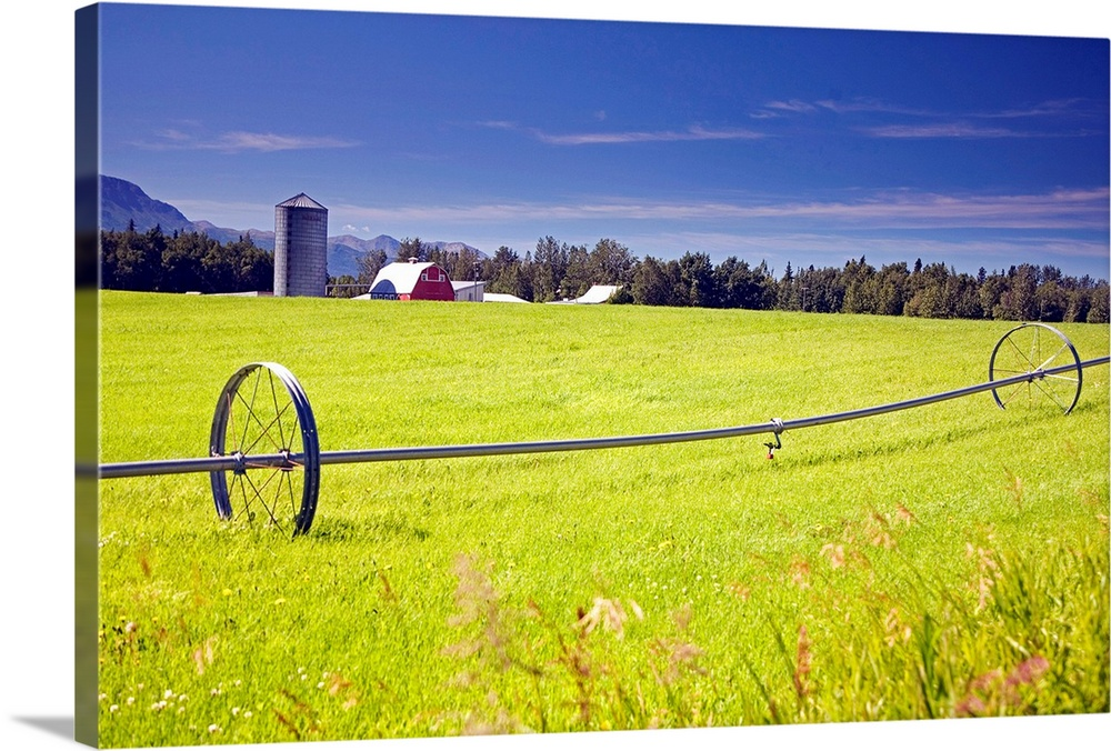 Large Solid-Faced Canvas Print Wall Art Print 30 x 20 entitled Rolling irrigation sprinkler on hay field w/farm background... Solid-Faced Canvas Print entitled Rolling irrigation sprinkler on hay field wfarm background, Mat Su Valley, Alaska.  A vast open field is pictured with a barn in the background and a large sprinkler rolling across the grass.  Multiple sizes available.  Primary colors within this image include Dark Yellow, White, Lime Green, Dark Navy Blue.  Made in USA.  Satisfaction guaranteed.  Inks used are latex-based and designed to last.  Canvas depth is 1.25 and includes a finished backing with pre-installed hanging hardware.  Canvas is handcrafted and made-to-order in the United States using high quality artist-grade canvas.