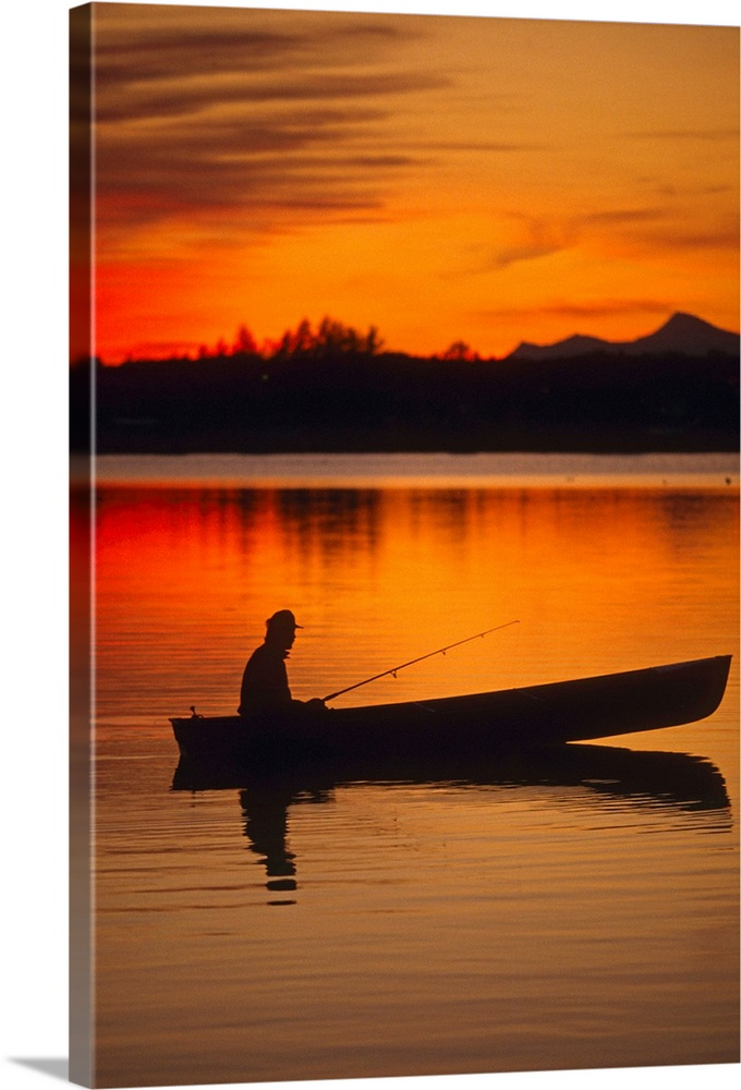 Large Solid-Faced Canvas Print Wall Art Print 20 x 30 entitled Silhouetted Fisherman sits in his boat at Sunset Solid-Faced Canvas Print entitled Silhouetted Fisherman sits in his boat at Sunset.  Multiple sizes available.  Primary colors within this image include Red, Orange, Dark Red, Black.  Made in USA.  Satisfaction guaranteed.  Inks used are latex-based and designed to last.  Canvas depth is 1.25 and includes a finished backing with pre-installed hanging hardware.  Featuring a proprietary design, our canvases produce the tightest corners without any bubbles, ripples, or bumps and will not warp or sag over time.