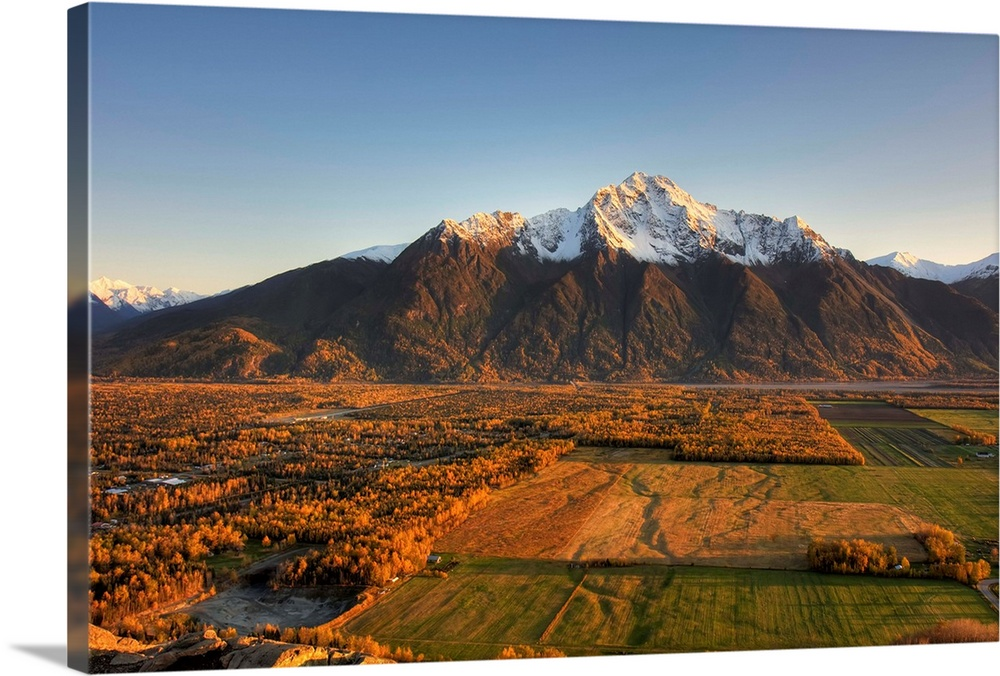 Large Solid-Faced Canvas Print Wall Art Print 30 x 20 entitled Sunset on Pioneer Peak and farm fields near Palmer, Alaska ... Solid-Faced Canvas Print entitled Sunset on Pioneer Peak and farm fields near Palmer, Alaska during Autumn.  Multiple sizes available.  Primary colors within this image include Brown, Black, White, Gray Blue.  Made in the USA.  Satisfaction guaranteed.  Inks used are latex-based and designed to last.  Featuring a proprietary design, our canvases produce the tightest corners without any bubbles, ripples, or bumps and will not warp or sag over time.  Canvas depth is 1.25 and includes a finished backing with pre-installed hanging hardware.