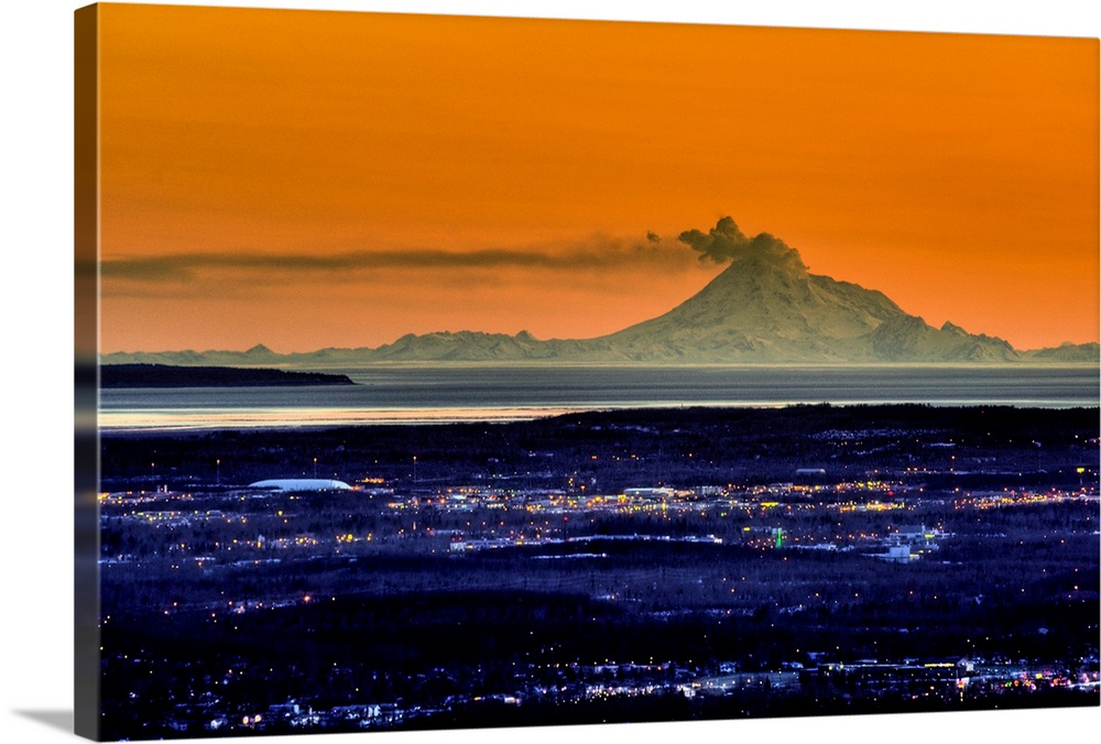 Large Solid-Faced Canvas Print Wall Art Print 30 x 20 entitled The city of Anchorage Alaska at sunset with Mount Redoubt e... Solid-Faced Canvas Print entitled The city of Anchorage Alaska at sunset with Mount Redoubt erupting in the background.  Multiple sizes available.  Primary colors within this image include Orange, Dark Blue, Light Yellow, Black.  Made in USA.  All products come with a 365 day workmanship guarantee.  Archival-quality UV-resistant inks.  Archival inks prevent fading and preserve as much fine detail as possible with no over-saturation or color shifting.  Featuring a proprietary design, our canvases produce the tightest corners without any bubbles, ripples, or bumps and will not warp or sag over time.
