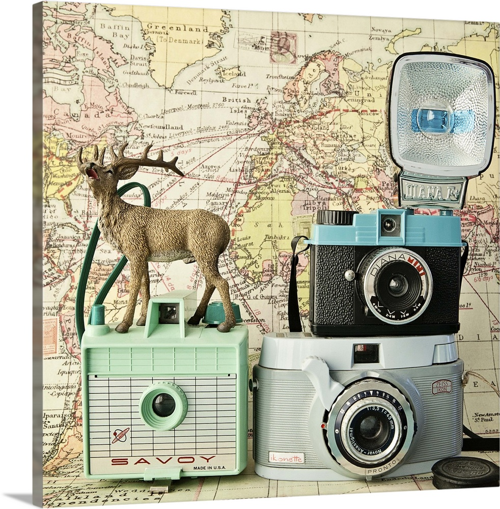 Large Solid-Faced Canvas Print Wall Art Print 20 x 20 entitled Happy Travels Solid-Faced Canvas Print entitled Happy Travels.  A toy deer on a set of three vintage cameras with a map backdrop.  Multiple sizes available.  Primary colors within this image include Peach, Black, Gray.  Made in the USA.  Satisfaction guaranteed.  Inks used are latex-based and designed to last.  Canvas is handcrafted and made-to-order in the United States using high quality artist-grade canvas.  Featuring a proprietary design, our canvases produce the tightest corners without any bubbles, ripples, or bumps and will not warp or sag over time.