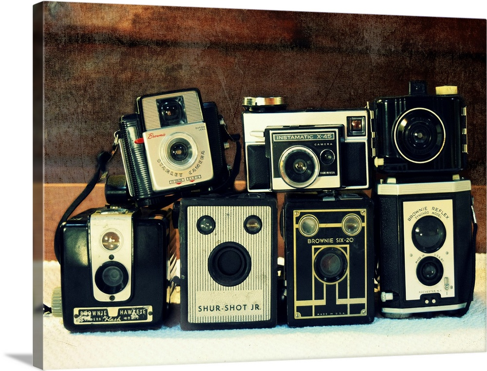 Large Solid-Faced Canvas Print Wall Art Print 24 x 18 entitled Vintage Camera Collection Solid-Faced Canvas Print entitled Vintage Camera Collection.  Photograph of stacked vintage cameras.  Multiple sizes available.  Primary colors within this image include Peach, Black, White, Dark Forest Green.  Made in USA.  Satisfaction guaranteed.  Archival-quality UV-resistant inks.  Canvas depth is 1.25 and includes a finished backing with pre-installed hanging hardware.  Canvas is handcrafted and made-to-order in the United States using high quality artist-grade canvas.
