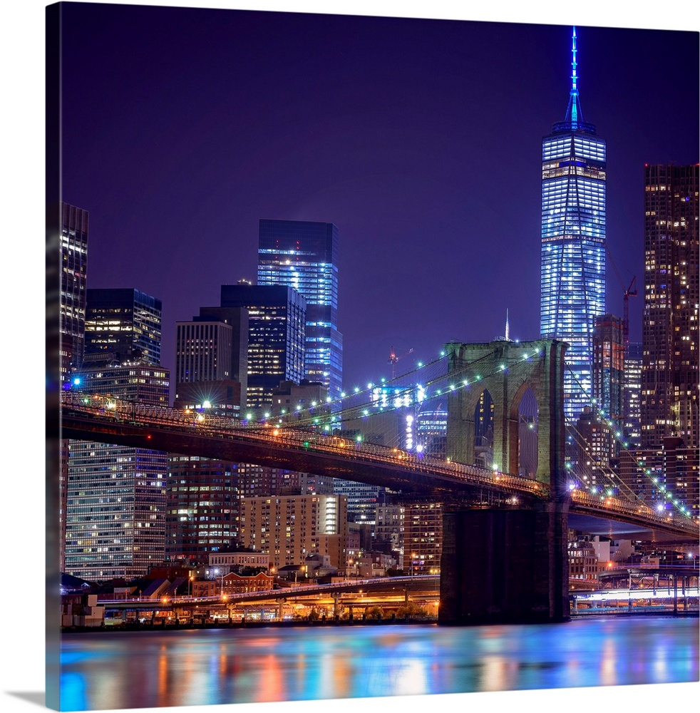 Large Solid-Faced Canvas Print Wall Art Print 24 x 24 entitled Brooklyn Bridge And Freedom Tower At Night Solid-Faced Canvas Print entitled Brooklyn Bridge And Freedom Tower At Night.  Multiple sizes available.  Primary colors within this image include Dark Red, Dark Blue, White, Royal Blue.  Made in USA.  All products come with a 365 day workmanship guarantee.  Archival-quality UV-resistant inks.  Featuring a proprietary design, our canvases produce the tightest corners without any bubbles, ripples, or bumps and will not warp or sag over time.  Canvas is handcrafted and made-to-order in the United States using high quality artist-grade canvas.