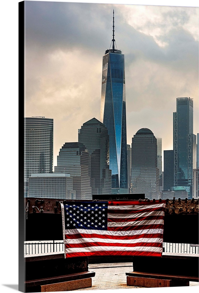 Large Solid-Faced Canvas Print Wall Art Print 24 x 36 entitled Freedom Tower And The Flag Solid-Faced Canvas Print entitled Freedom Tower And The Flag.  Multiple sizes available.  Primary colors within this image include Dark Red, Black, Light Gray, White.  Made in USA.  All products come with a 365 day workmanship guarantee.  Inks used are latex-based and designed to last.  Archival inks prevent fading and preserve as much fine detail as possible with no over-saturation or color shifting.  Canvas depth is 1.25 and includes a finished backing with pre-installed hanging hardware.