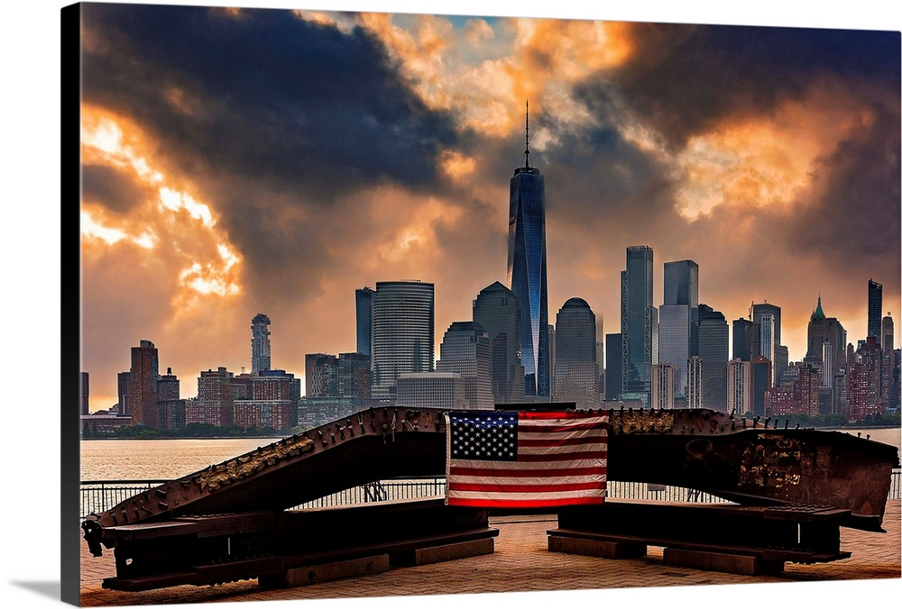 Large Solid-Faced Canvas Print Wall Art Print 36 x 24 entitled Freedom Tower And The Flag Solid-Faced Canvas Print entitled Freedom Tower And The Flag.  Multiple sizes available.  Primary colors within this image include Dark Red, Dark Blue, Peach, Black.  Made in the USA.  All products come with a 365 day workmanship guarantee.  Archival-quality UV-resistant inks.  Canvas depth is 1.25 and includes a finished backing with pre-installed hanging hardware.  Featuring a proprietary design, our canvases produce the tightest corners without any bubbles, ripples, or bumps and will not warp or sag over time.