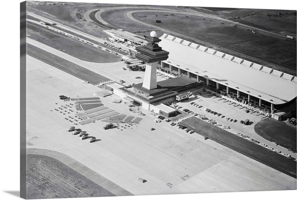 Large Gallery-Wrapped Canvas Wall Art Print 30 x 20 entitled Dulles International Airport From Afar Gallery-Wrapped Canvas entitled Dulles International Airport From Afar.  This is an aerial view of the tower and main building at the Dulles International Airport which will be dedicated by President Kennedy on Saturday. At left, in this picture made today, seats for the ceremony and the speakers platform are erected.  Multiple sizes available.  Primary colors within this image include Dark Gray, Silver.  Made in the USA.  All products come with a 365 day workmanship guarantee.  Inks used are latex-based and designed to last.  Canvas is designed to prevent fading.  Canvas is a 65 polyester, 35 cotton base, with two acrylic latex primer basecoats and a semi-gloss inkjet receptive topcoat.