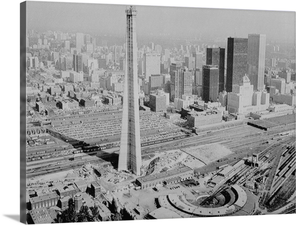 Large Gallery-Wrapped Canvas Wall Art Print 30 x 23 entitled The CN Tower in Toronto in 1973 Gallery-Wrapped Canvas entitled The CN Tower in Toronto in 1973.  The CN Tower in Toronto in 1973. The structure houses radio, microwave, and television broadcast facilities as well as an observation deck and restaurant.  Multiple sizes available.  Primary colors within this image include Dark Gray, Silver.  Made in the USA.  Satisfaction guaranteed.  Archival-quality UV-resistant inks.  Museum-quality, artist-grade canvas mounted on sturdy wooden stretcher bars 1.5 thick.  Comes ready to hang.  Canvases have a UVB protection built in to protect against fading and moisture and are designed to last for over 100 years.