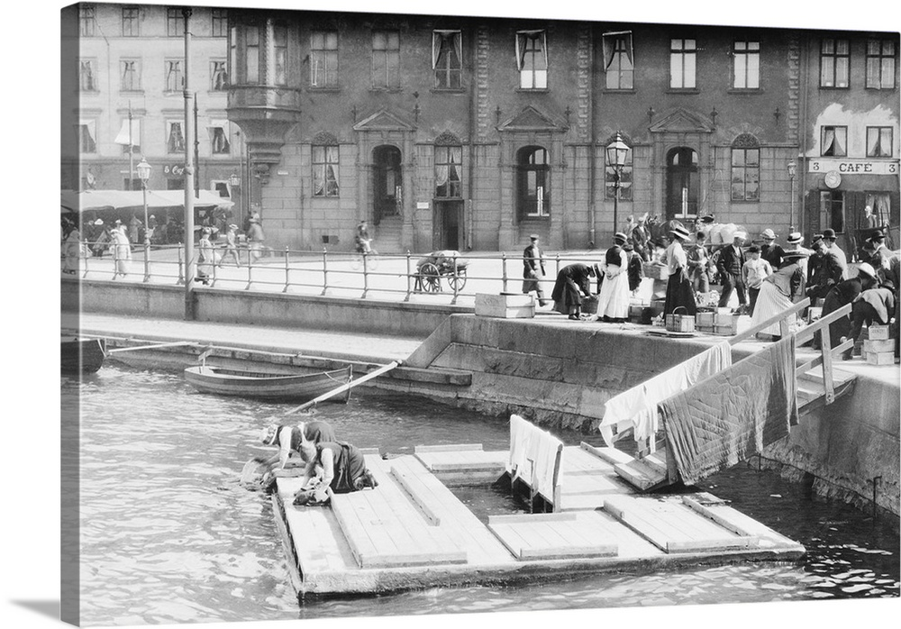 Large Gallery-Wrapped Canvas Wall Art Print 24 x 16 entitled Women Washing Clothes In Canal Gallery-Wrapped Canvas entitled Women Washing Clothes In Canal.  Women washing clothes in canal in Stockholm.  Multiple sizes available.  Primary colors within this image include Black, Gray, White.  Made in the USA.  Satisfaction guaranteed.  Archival-quality UV-resistant inks.  Canvas is a 65 polyester, 35 cotton base, with two acrylic latex primer basecoats and a semi-gloss inkjet receptive topcoat.  Canvas is acid-free and 20 millimeters thick.