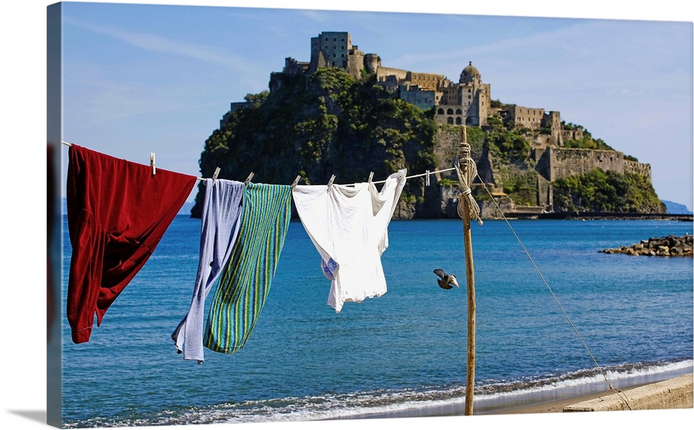 Large Gallery-Wrapped Canvas Wall Art Print 24 x 15 entitled Italy, Campania, Ischia Island, Ischia Ponte, Aragonese castl... Gallery-Wrapped Canvas entitled Italy, Campania, Ischia Island, Ischia Ponte, Aragonese castle with fishermans clothes.  Italy, Campania, Napoli district, Mediterranean sea, Tyrrhenian sea, Tyrrhenian coast, Ischia Island, Ischia Ponte, Aragonese castle with fishermans clothes.  Multiple sizes available.  Primary colors within this image include Black, Muted Blue, Pale Blue.  Made in the USA.  All products come with a 365 day workmanship guarantee.  Archival-quality UV-resistant inks.  Museum-quality, artist-grade canvas mounted on sturdy wooden stretcher bars 1.5 thick.  Comes ready to hang.  Canvas frames are built with farmed or reclaimed domestic pine or poplar wood.