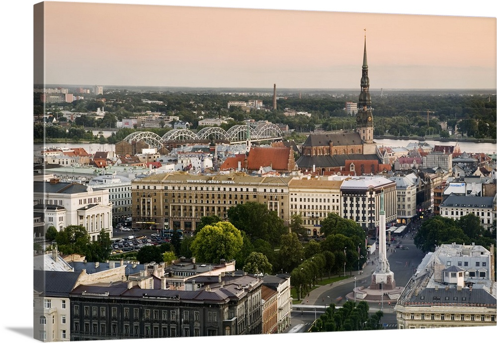Large Solid-Faced Canvas Print Wall Art Print 36 x 24 entitled Latvia, Riga, Cityscape with view of the Freedom Monument a... Solid-Faced Canvas Print entitled Latvia, Riga, Cityscape with view of the Freedom Monument and St Peters Church.  Multiple sizes available.  Primary colors within this image include Dark Yellow, Black, Gray, Silver.  Made in the USA.  Satisfaction guaranteed.  Inks used are latex-based and designed to last.  Canvas is handcrafted and made-to-order in the United States using high quality artist-grade canvas.  Featuring a proprietary design, our canvases produce the tightest corners without any bubbles, ripples, or bumps and will not warp or sag over time.