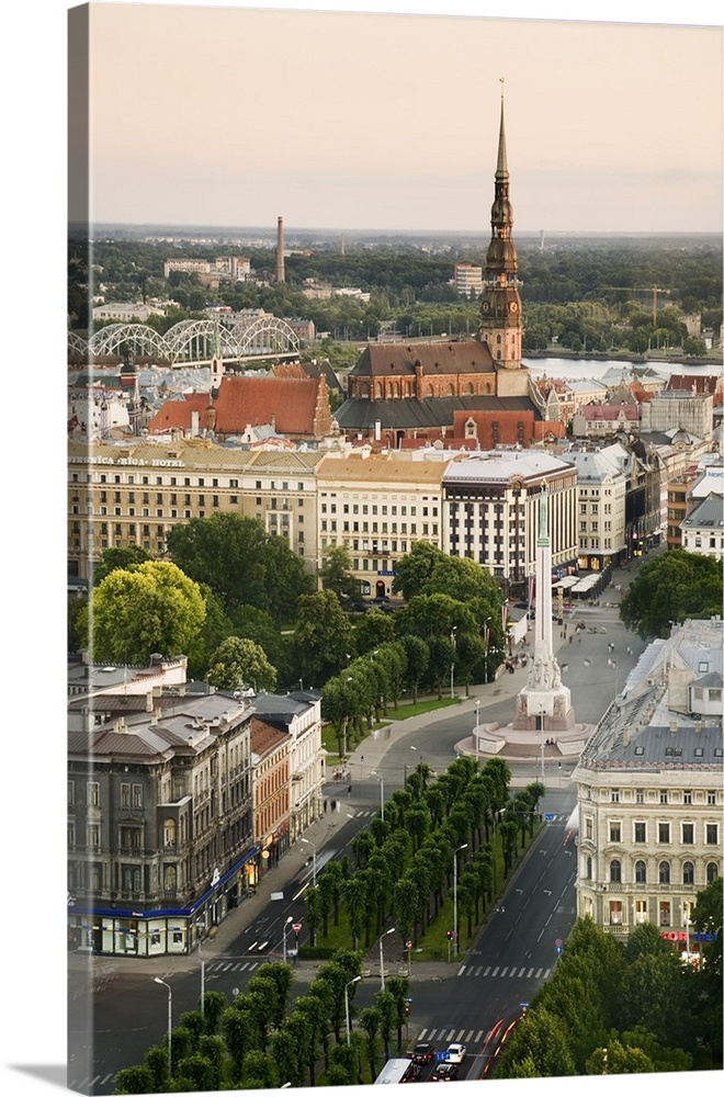 Large Solid-Faced Canvas Print Wall Art Print 24 x 36 entitled Latvia, Riga, Cityscape with view of the Freedom Monument a... Solid-Faced Canvas Print entitled Latvia, Riga, Cityscape with view of the Freedom Monument and St Peters Church.  Multiple sizes available.  Primary colors within this image include Dark Yellow, Black, Gray, White.  Made in USA.  Satisfaction guaranteed.  Inks used are latex-based and designed to last.  Canvas depth is 1.25 and includes a finished backing with pre-installed hanging hardware.  Canvas is handcrafted and made-to-order in the United States using high quality artist-grade canvas.