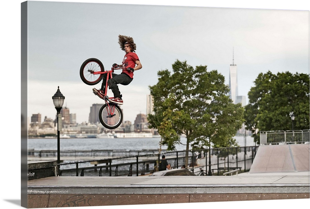 Large Solid-Faced Canvas Print Wall Art Print 36 x 24 entitled New Jersey, Hoboken, BMX biker at Castle Point Skate Park Solid-Faced Canvas Print entitled New Jersey, Hoboken, BMX biker at Castle Point Skate Park.  USA, New Jersey, Hoboken, BMX biker at Castle Point Skate Park with the Freedom Tower in the background.  Multiple sizes available.  Primary colors within this image include White, Dark Forest Green.  Made in the USA.  All products come with a 365 day workmanship guarantee.  Inks used are latex-based and designed to last.  Featuring a proprietary design, our canvases produce the tightest corners without any bubbles, ripples, or bumps and will not warp or sag over time.  Canvas depth is 1.25 and includes a finished backing with pre-installed hanging hardware.
