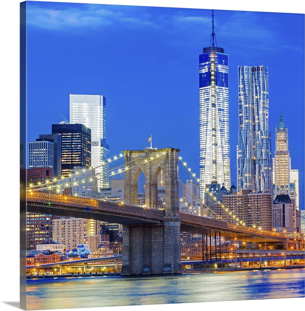 Large Solid-Faced Canvas Print Wall Art Print 24 x 24 entitled New York City, East River, Lower Manhattan, Brooklyn Bridge Solid-Faced Canvas Print entitled New York City, East River, Lower Manhattan, Brooklyn Bridge.  USA, New York City, East River, Manhattan, Lower Manhattan, Brooklyn Bridge, Downtown Manhattan with Freedom Tower and Beekman Tower at night.  Multiple sizes available.  Primary colors within this image include Brown, Dark Blue, Peach, Dark Navy Blue.  Made in USA.  All products come with a 365 day workmanship guarantee.  Archival-quality UV-resistant inks.  Archival inks prevent fading and preserve as much fine detail as possible with no over-saturation or color shifting.  Canvas is handcrafted and made-to-order in the United States using high quality artist-grade canvas.
