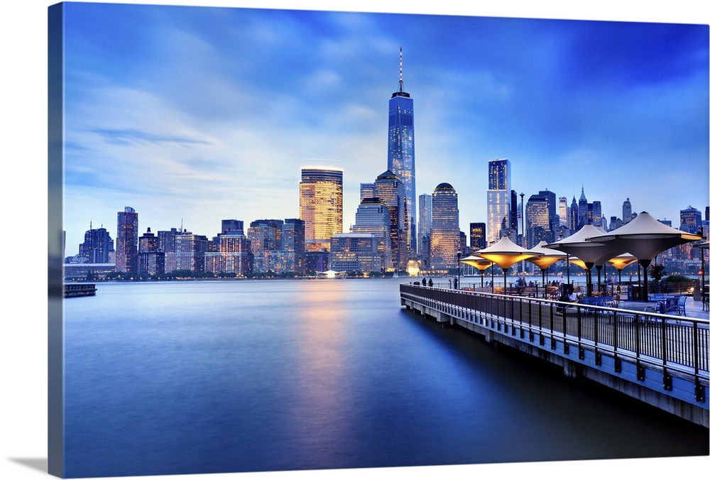 Large Solid-Faced Canvas Print Wall Art Print 36 x 24 entitled New York City, freedom tower, new jersey, Manhattan Solid-Faced Canvas Print entitled New York City, freedom tower, new jersey, Manhattan.  USA, New York City, freedom tower, new jersey, Manhattan, wooden pier, Manhattan, Lower Manhattan, One World Trade Center, Freedom Tower, City skyline at dusk from J Owen Grundy park.  Multiple sizes available.  Primary colors within this image include Blue, Black, Pale Blue, Royal Blue.  Made in USA.  All products come with a 365 day workmanship guarantee.  Archival-quality UV-resistant inks.  Featuring a proprietary design, our canvases produce the tightest corners without any bubbles, ripples, or bumps and will not warp or sag over time.  Canvas depth is 1.25 and includes a finished backing with pre-installed hanging hardware.