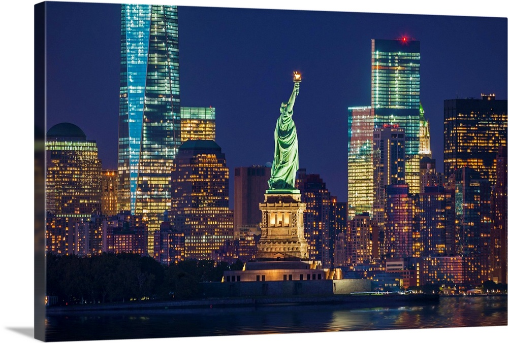 Large Solid-Faced Canvas Print Wall Art Print 36 x 24 entitled New York City, Liberty Island, Manhattan Skyline And Statue... Solid-Faced Canvas Print entitled New York City, Liberty Island, Manhattan Skyline And Statue Of Liberty At Night.  USA, New York City, Manhattan, Lower Manhattan, Liberty Island, Statue of Liberty, Lower Manhattan skyline with Freedom Tower and Statue of Liberty at night.  Multiple sizes available.  Primary colors within this image include Brown, Peach, Black, White.  Made in USA.  All products come with a 365 day workmanship guarantee.  Inks used are latex-based and designed to last.  Canvas is handcrafted and made-to-order in the United States using high quality artist-grade canvas.  Featuring a proprietary design, our canvases produce the tightest corners without any bubbles, ripples, or bumps and will not warp or sag over time.
