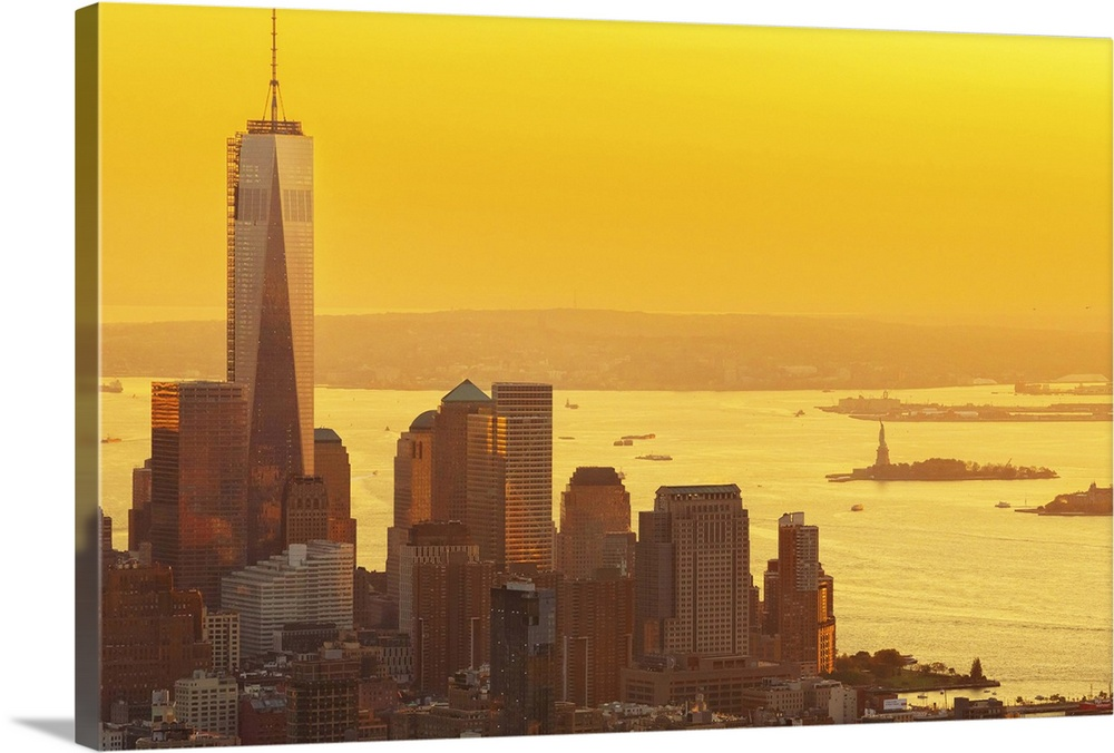 Large Solid-Faced Canvas Print Wall Art Print 36 x 24 entitled New York City, Lower Manhattan, One World Trade Center, Fre... Solid-Faced Canvas Print entitled New York City, Lower Manhattan, One World Trade Center, Freedom Tower.  USA, New York City, Manhattan, Lower Manhattan, One World Trade Center, Freedom Tower, Lower Manhattan skyline with Freedom Tower and Statue of Liberty at sunset, view from the Empire State Building.  Multiple sizes available.  Primary colors within this image include Brown, Light Yellow, Dark Forest Green.  Made in USA.  Satisfaction guaranteed.  Inks used are latex-based and designed to last.  Canvas depth is 1.25 and includes a finished backing with pre-installed hanging hardware.  Canvas is handcrafted and made-to-order in the United States using high quality artist-grade canvas.