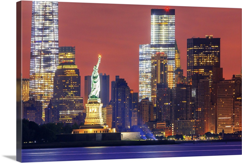 Large Solid-Faced Canvas Print Wall Art Print 36 x 24 entitled New York City, Manhattan, Liberty Island, Statue of Liberty Solid-Faced Canvas Print entitled New York City, Manhattan, Liberty Island, Statue of Liberty.  USA, New York City, Manhattan, Lower Manhattan, Liberty Island, Statue of Liberty, Lower Manhattan with Freedom Tower and Statue of Liberty at sunset.  Multiple sizes available.  Primary colors within this image include Orange, Pink, Light Yellow, White.  Made in USA.  Satisfaction guaranteed.  Inks used are latex-based and designed to last.  Canvas depth is 1.25 and includes a finished backing with pre-installed hanging hardware.  Canvas is handcrafted and made-to-order in the United States using high quality artist-grade canvas.