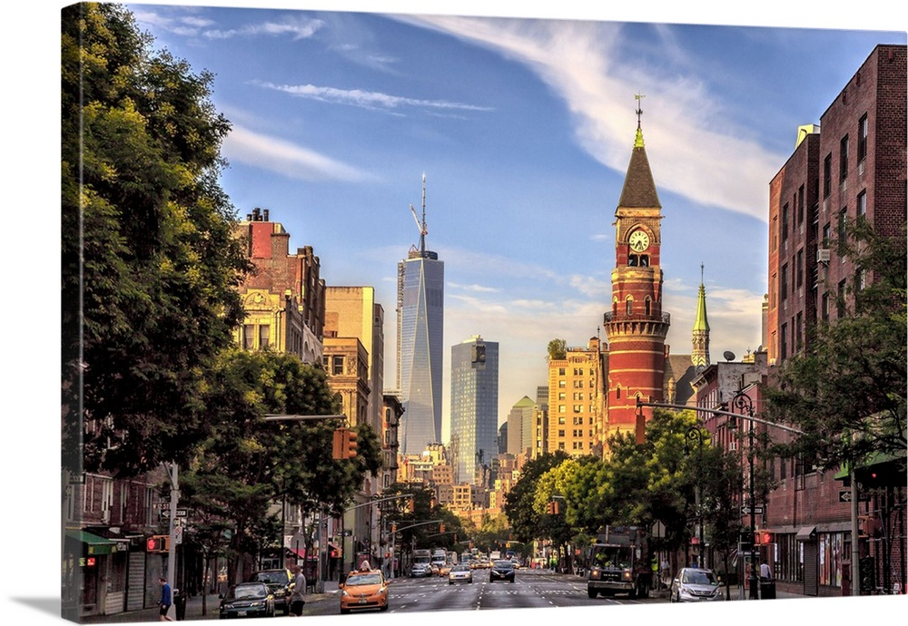 Large Solid-Faced Canvas Print Wall Art Print 36 x 24 entitled New York City, View down 6th Avenue Solid-Faced Canvas Print entitled New York City, View down 6th Avenue.  New York, New York City City, View down 6th Avenue with Jefferson Market Library and Freedom Tower.  Multiple sizes available.  Primary colors within this image include Peach, Sky Blue, Black, Gray.  Made in USA.  All products come with a 365 day workmanship guarantee.  Inks used are latex-based and designed to last.  Canvas depth is 1.25 and includes a finished backing with pre-installed hanging hardware.  Canvas is handcrafted and made-to-order in the United States using high quality artist-grade canvas.