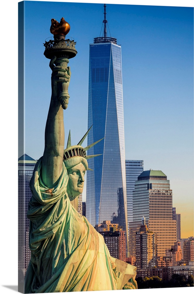 Large Solid-Faced Canvas Print Wall Art Print 24 x 36 entitled USA, New York City, Manhattan, Liberty Island, Statue Of Li... Solid-Faced Canvas Print entitled USA, New York City, Manhattan, Liberty Island, Statue Of Liberty And Freedom Tower.  USA, New York City, Manhattan, Lower Manhattan, Liberty Island, Statue of Liberty, Statue of Liberty and Freedom Tower.  Multiple sizes available.  Primary colors within this image include Peach, Royal Blue, Dark Navy Blue, Light Gray Blue.  Made in USA.  Satisfaction guaranteed.  Archival-quality UV-resistant inks.  Featuring a proprietary design, our canvases produce the tightest corners without any bubbles, ripples, or bumps and will not warp or sag over time.  Archival inks prevent fading and preserve as much fine detail as possible with no over-saturation or color shifting.