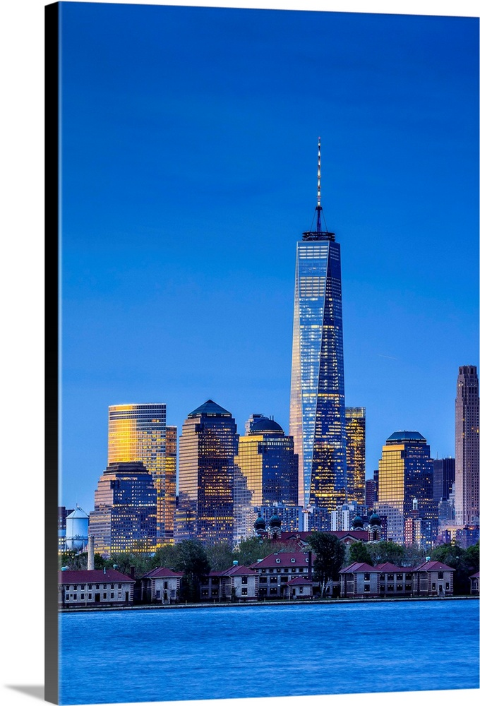 Large Solid-Faced Canvas Print Wall Art Print 24 x 36 entitled USA, New York City, View Towards The One World Trade Center... Solid-Faced Canvas Print entitled USA, New York City, View Towards The One World Trade Center, Freedom Tower, At Night.  USA, New York City, Manhattan, Lower Manhattan, One World Trade Center, Freedom Tower, The Ellis Island, view from New Jersey towards Lower Manhattan, with the One World Trade Center, with Freedom Tower, at night.  Multiple sizes available.  Primary colors within this image include Dark Blue, Light Yellow, Black, Royal Blue.  Made in the USA.  All products come with a 365 day workmanship guarantee.  Inks used are latex-based and designed to last.  Canvas depth is 1.25 and includes a finished backing with pre-installed hanging hardware.  Canvas is handcrafted and made-to-order in the United States using high quality artist-grade canvas.
