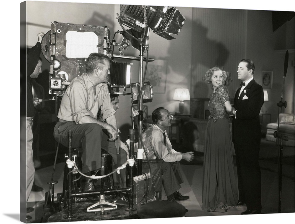 Large Solid-Faced Canvas Print Wall Art Print 40 x 30 entitled Camera man Don Clark and Director James Tinling film a scen... Solid-Faced Canvas Print entitled Camera man Don Clark and Director James Tinling film a scene for Change of Heart.  Camera man Don Clark and Director James Tinling film a scene for Change of Heart with Lyle Talbot and Gloria Stuart. 20th Century Fox. c. 1938.  Multiple sizes available.  Primary colors within this image include Dark Gray, Silver.  Made in USA.  Satisfaction guaranteed.  Inks used are latex-based and designed to last.  Featuring a proprietary design, our canvases produce the tightest corners without any bubbles, ripples, or bumps and will not warp or sag over time.  Canvas is handcrafted and made-to-order in the United States using high quality artist-grade canvas.