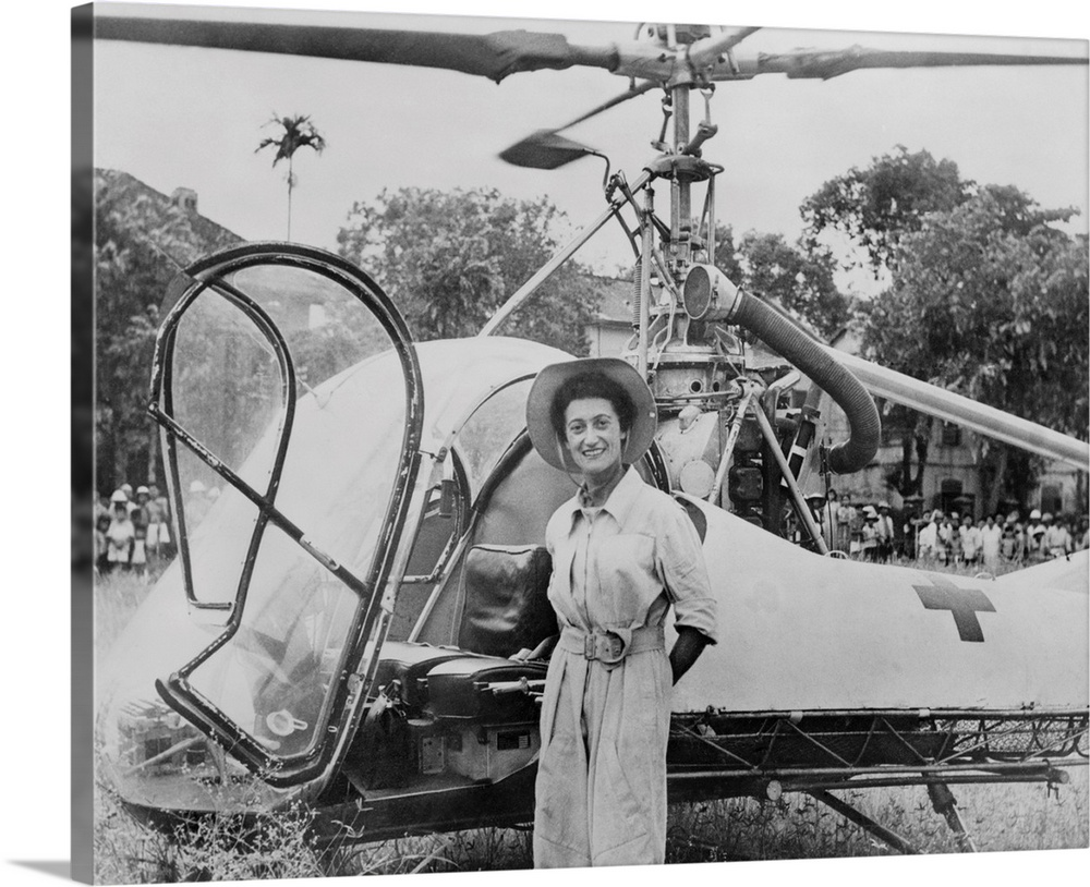 Large Gallery-Wrapped Canvas Wall Art Print 20 x 16 entitled Dr. Valerie Andre, in front of her helicopter in Tonkin, Vietnam Gallery-Wrapped Canvas entitled Dr. Valerie Andre in front of her helicopter in Tonkin Vietnam.  Dr. Valerie Andre in front of her helicopter in Tonkin Vietnam in 1952. She served in the French army as a neurosurgeon and learned to fly helicopters to reach wounded soldiers. From 1952-53 she rescued 165 soldiers and parachuted to treat wounded needing immediate surgery. In 1976 she became the first Women to reach the rank of General Officer in the French Army.  Multiple sizes available.  Primary colors within this image include Dark Gray Silver.  Made in the USA.  All products come with a 365 day workmanship guarantee.  Inks used are latex-based and designed to last.  Canvas frames are built with farmed or reclaimed domestic pine or poplar wood.  Canvas is a 65 polyester 35 cotton base with two acrylic latex primer basecoats and a semi-gloss inkjet receptive topcoat.
