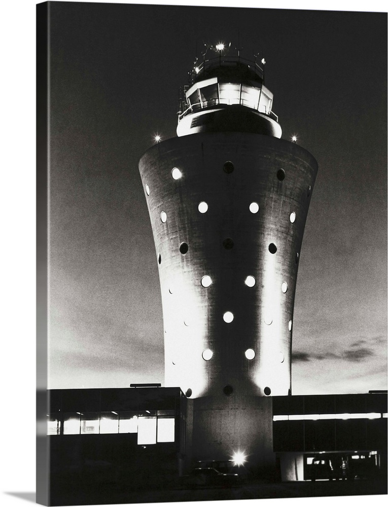 Large Solid-Faced Canvas Print Wall Art Print 30 x 40 entitled La Guardia Airport control tower, constructed in 1962 Solid-Faced Canvas Print entitled La Guardia Airport control tower, constructed in 1962.  La Guardia Airport control tower, constructed in 1962. Designed by Wallace K. Harrison, its futuristic design would be at home with the Trylon and Perisphere he designed for the 1939 Worlds Fair. In 2010 it was replaced by a new tower with advanced electronics and better views of the runways.  Multiple sizes available.  Primary colors within this image include Dark Gray, White.  Made in the USA.  All products come with a 365 day workmanship guarantee.  Inks used are latex-based and designed to last.  Canvas depth is 1.25 and includes a finished backing with pre-installed hanging hardware.  Featuring a proprietary design, our canvases produce the tightest corners without any bubbles, ripples, or bumps and will not warp or sag over time.
