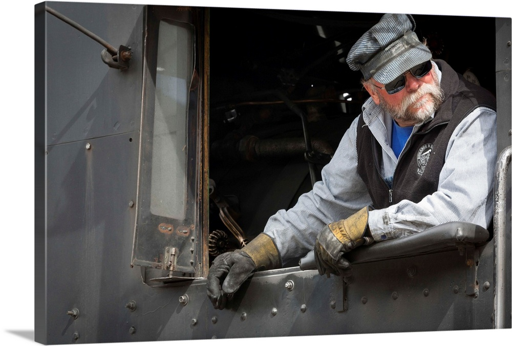 Large Gallery-Wrapped Canvas Wall Art Print 24 x 16 entitled Train Conductor I Gallery-Wrapped Canvas entitled Train Conductor I.  Photograph of a train engineer in vintage clothes.  Multiple sizes available.  Primary colors within this image include Black, Gray, White.  Made in USA.  All products come with a 365 day workmanship guarantee.  Inks used are latex-based and designed to last.  Museum-quality, artist-grade canvas mounted on sturdy wooden stretcher bars 1.5 thick.  Comes ready to hang.  Canvases are stretched across a 1.5 inch thick wooden frame with easy-to-mount hanging hardware.