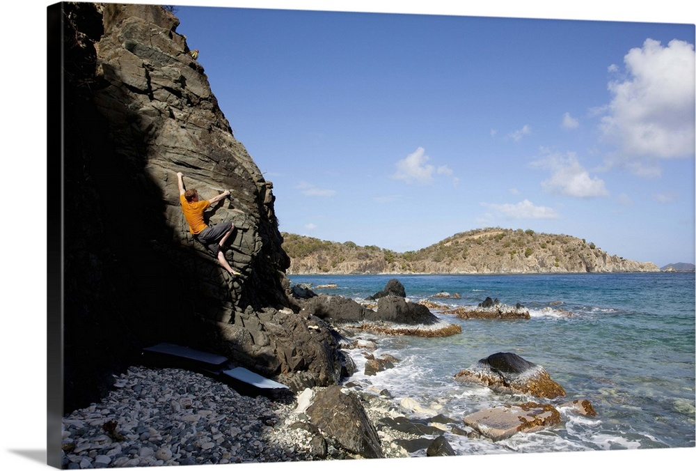 Large Solid-Faced Canvas Print Wall Art Print 30 x 20 entitled A man climbs out of the shadow on a beach boulder problem i... Solid-Faced Canvas Print entitled A man climbs out of the shadow on a beach boulder problem in the Caribbean..  Multiple sizes available.  Primary colors within this image include Orange, Sky Blue, Black, Dark Forest Green.  Made in the USA.  All products come with a 365 day workmanship guarantee.  Inks used are latex-based and designed to last.  Archival inks prevent fading and preserve as much fine detail as possible with no over-saturation or color shifting.  Canvas depth is 1.25 and includes a finished backing with pre-installed hanging hardware.