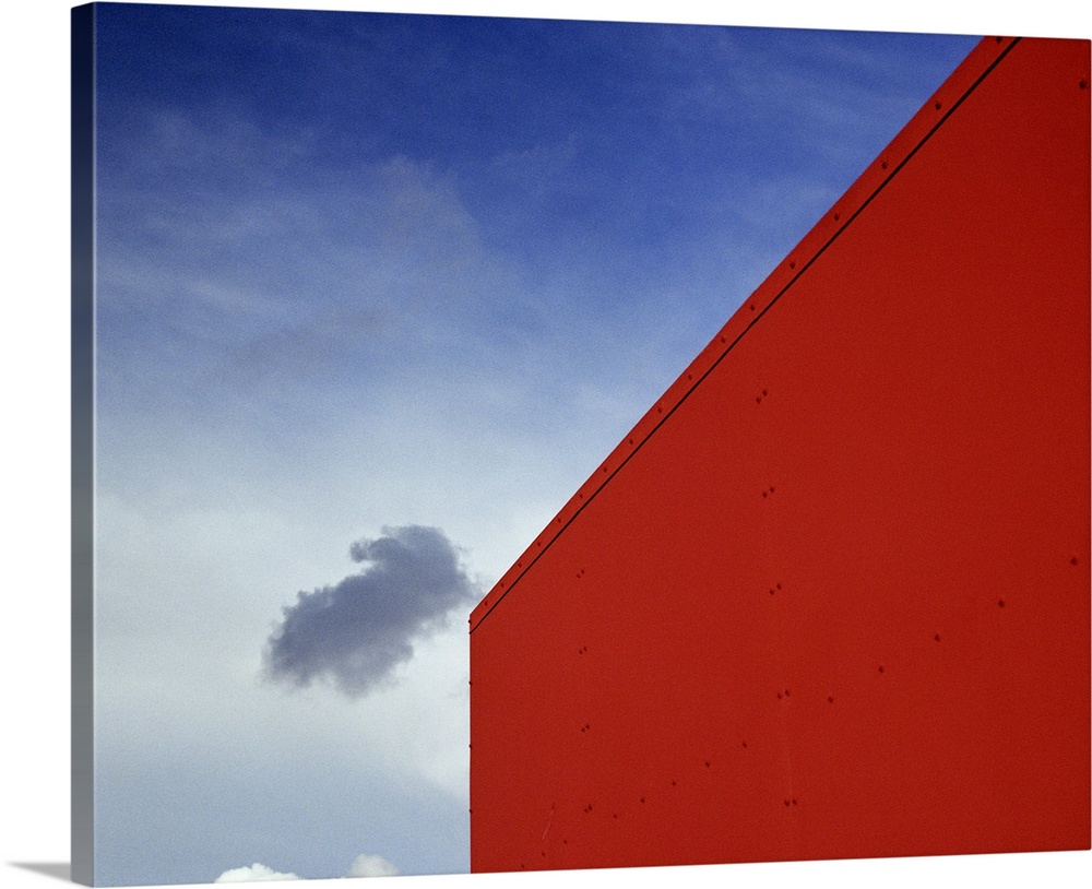 Large Solid-Faced Canvas Print Wall Art Print 30 x 24 entitled A shadowed cloud floating through blue sky over the red cor... Solid-Faced Canvas Print entitled A shadowed cloud floating through blue sky over the red corner of James John School..  Multiple sizes available.  Primary colors within this image include Dark Red, Dark Blue, Silver, Royal Blue.  Made in the USA.  All products come with a 365 day workmanship guarantee.  Inks used are latex-based and designed to last.  Canvas is handcrafted and made-to-order in the United States using high quality artist-grade canvas.  Archival inks prevent fading and preserve as much fine detail as possible with no over-saturation or color shifting.