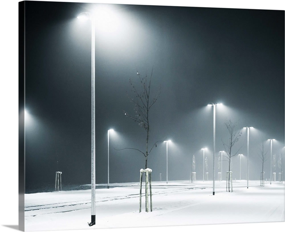 Large Solid-Faced Canvas Print Wall Art Print 30 x 24 entitled An empty, snow-covered parking lot at night time. Solid-Faced Canvas Print entitled An empty, snow-covered parking lot at night time..  Multiple sizes available.  Primary colors within this image include Dark Gray, White.  Made in USA.  Satisfaction guaranteed.  Inks used are latex-based and designed to last.  Canvas depth is 1.25 and includes a finished backing with pre-installed hanging hardware.  Canvas is handcrafted and made-to-order in the United States using high quality artist-grade canvas.