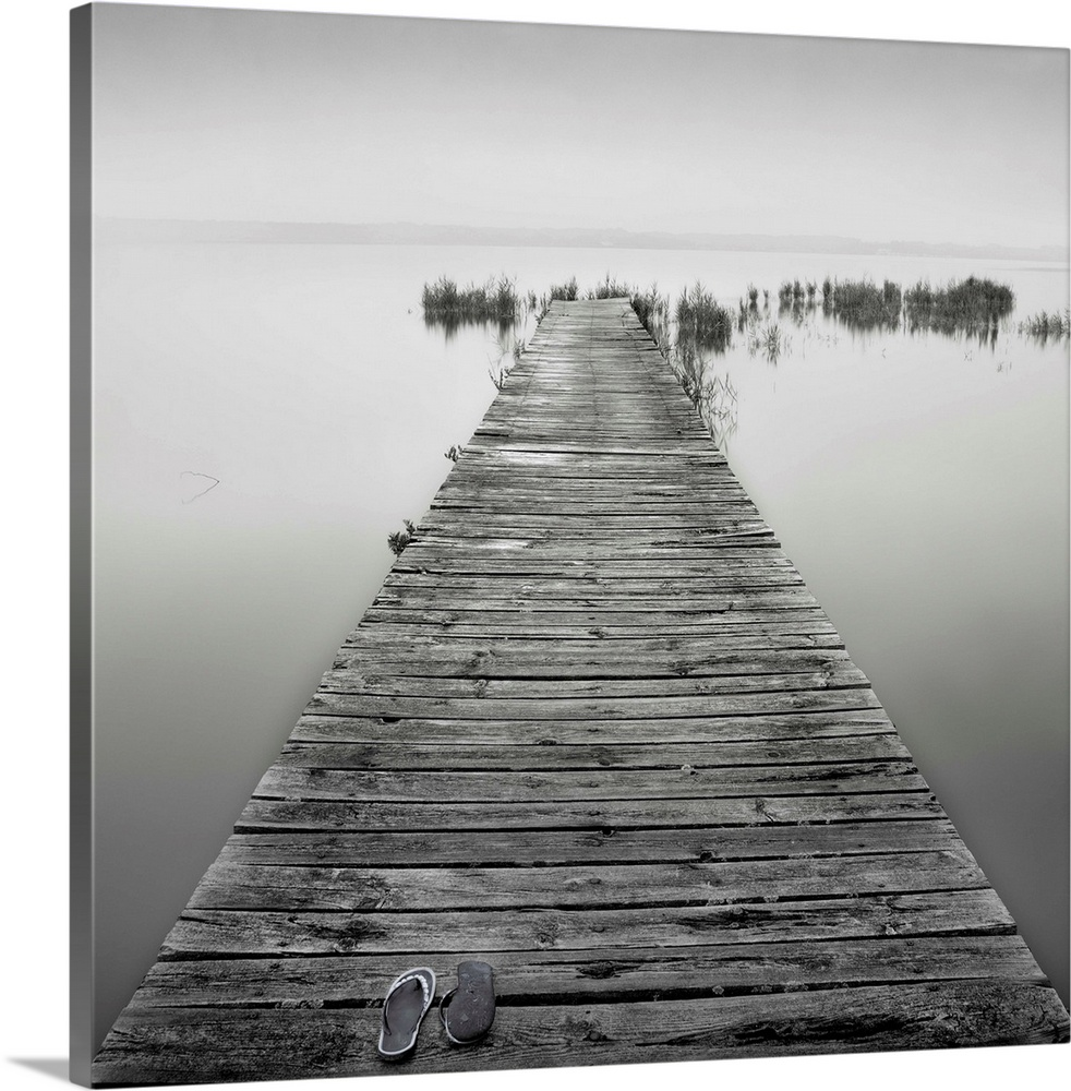 Large Solid-Faced Canvas Print Wall Art Print 20 x 20 entitled An old wooden jetty on a very calm lake. A pair of shoes ar... Solid-Faced Canvas Print entitled An old wooden jetty on a very calm lake. A pair of shoes are also lying on the jetty..  Multiple sizes available.  Primary colors within this image include Black, Gray, Silver.  Made in USA.  Satisfaction guaranteed.  Archival-quality UV-resistant inks.  Archival inks prevent fading and preserve as much fine detail as possible with no over-saturation or color shifting.  Featuring a proprietary design, our canvases produce the tightest corners without any bubbles, ripples, or bumps and will not warp or sag over time.