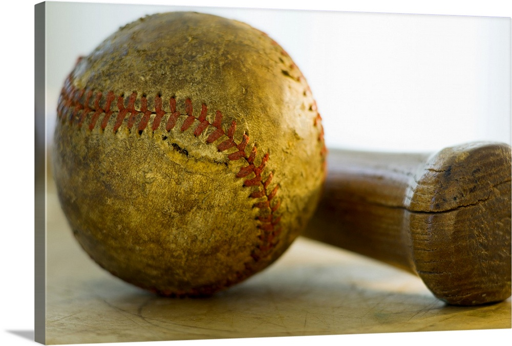 Large Gallery-Wrapped Canvas Wall Art Print 24 x 16 entitled Antique baseball with baseball bat Gallery-Wrapped Canvas entitled Antique baseball with baseball bat.  Huge photograph focuses on a stitched ball of worn cowhide sitting next to a wooden hitting instrument on a table.  Both of these pieces of equipment are used in the sport nicknamed Americas Pastime.  .  Multiple sizes available.  Primary colors within this image include Brown Dark Yellow Peach Black.  Made in the USA.  Satisfaction guaranteed.  Archival-quality UV-resistant inks.  Canvas is a 65 polyester 35 cotton base with two acrylic latex primer basecoats and a semi-gloss inkjet receptive topcoat.  Canvases have a UVB protection built in to protect against fading and moisture and are designed to last for over 100 years.