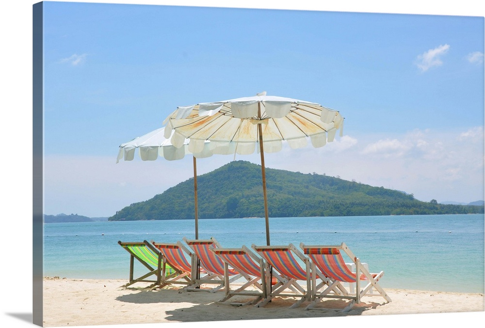 Large Solid-Faced Canvas Print Wall Art Print 30 x 20 entitled Beach chair and umbrella on beach and Rang Yai Island backg... Solid-Faced Canvas Print entitled Beach chair and umbrella on beach and Rang Yai Island background..  Multiple sizes available.  Primary colors within this image include Pink, Sky Blue, Gray, White.  Made in USA.  Satisfaction guaranteed.  Archival-quality UV-resistant inks.  Featuring a proprietary design, our canvases produce the tightest corners without any bubbles, ripples, or bumps and will not warp or sag over time.  Canvas depth is 1.25 and includes a finished backing with pre-installed hanging hardware.